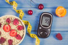 Glucose meter, oatmeal with fruits and centimeter, concept of checking sugar level, diabetes and healthy lifestyle. Glucometer, fresh oat flakes with fruits and Royalty Free Stock Photo