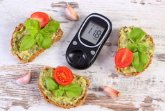 Glucometer and freshly sandwiches with paste of avocado, diabetes, healthy food and nutrition. Glucose meter with result of measurement sugar level and freshly Stock Photo