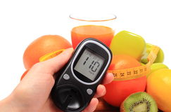 Glucometer, fruits, dumbbells, tape measure and glass of juice Stock Image