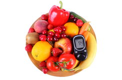 Glucometer with fruits and vegetables on wooden plate Royalty Free Stock Images