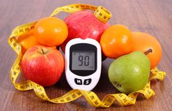 Glucose meter with tape measure and fresh fruits, diabetes, healthy nutrition and slimming concept. Glucometer with good result of measurement sugar level, tape stock images