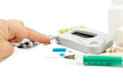 Glucometer with a hand, drugs and a syringe Stock Photos