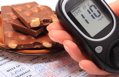 Glucometer in hand and portion of chocolate on medical form Stock Image