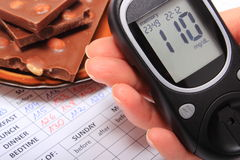 Glucometer in hand and portion of chocolate on medical form Royalty Free Stock Image