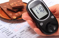 Glucometer in hand and portion of chocolate on medical form Royalty Free Stock Photo