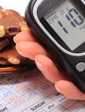 Glucometer in hand and portion of chocolate on medical form Stock Photos