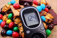 Glucometer with heap of sweets on jute burlap, diabetes and unhealthy food Royalty Free Stock Photography