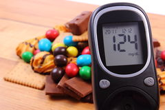 Glucometer with heap of sweets on wooden surface, diabetes and unhealthy food Stock Images