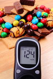 Glucometer with heap of sweets on wooden surface, diabetes and unhealthy food Stock Photos