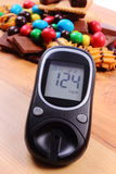 Glucometer with heap of sweets on wooden surface, diabetes and unhealthy food Royalty Free Stock Photography