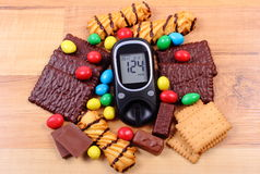 Glucometer with heap of sweets on wooden surface, diabetes and unhealthy food Stock Image