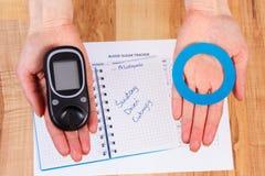 Glucometer i błękitny okrąg w ręce, symbol cukrzyk, światowy cukrzyca dzień zdjęcia stock