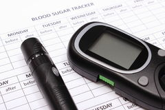 Glucometer and lancet device on empty medical forms for diabetes. Glucometer and lancet device lying on empty medical forms for measurement sugar in blood royalty free stock photo