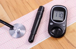 Glucometer with lancet device and stethoscope on electrocardiogram graph Royalty Free Stock Photography
