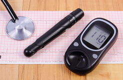 Glucometer with lancet device and stethoscope on electrocardiogram graph Stock Photo