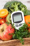 Glucometer for measuring sugar level and fruits and vegetables. Concept of diabetes, healthy lifestyles and nutrition royalty free stock images