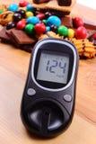 Glucometer med högen av sötsaker på träyttersida, sockersjuka och sjuklig mat Royaltyfri Fotografi