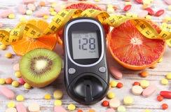 Glucometer med resultat, cm, frukter och läkarundersökningpreventivpillerar, sockersjuka, bantning, sund livsstil och näring arkivfoton