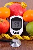 Glucometer med resultatsockernivån, cm och nya frukter, sockersjuka och sunt näringbegrepp Arkivbild