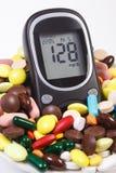 Glucometer mit Ergebniszuckergehalt und Haufen von medizinischen Pillen und von Kapseln, Diabetes, Gesundheitswesenkonzept Stockfotos