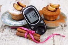 Glucometer, muffins met pruimen gepoederde suiker en kaneel, diabetes en heerlijk dessert Royalty-vrije Stock Foto's