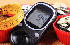 Glucometer, muffins in red cups and tape measure Royalty Free Stock Photography