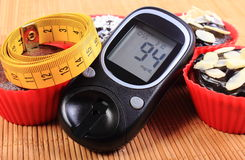 Glucometer, muffins in red cups and tape measure Royalty Free Stock Image