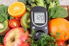 Glucometer para el nivel de medici?n del az?car con las frutas y verduras Concepto de diabetes, de formas de vida sanas y de nutr imagenes de archivo