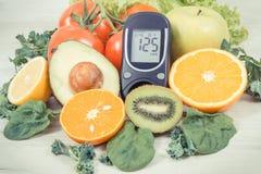 Glucometer para el nivel de medici?n del az?car y las frutas maduras con las verduras como bocado nutritivo sano que contiene las fotografía de archivo libre de regalías