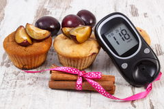 Glucometer, petits pains avec des prunes et des bâtons de cannelle sur le fond en bois, le diabète et le dessert délicieux Image libre de droits