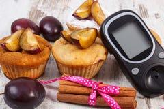 Glucometer, petits pains avec des prunes et des bâtons de cannelle sur le fond en bois, le diabète et le dessert délicieux Photographie stock libre de droits