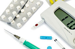 Glucometer with pills and a syringe Royalty Free Stock Photography