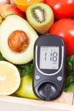 Glucometer pour le niveau de mesure de sucre et les fruits m?rs avec des l?gumes en tant que casse-cro?te nutritif sain contenant image libre de droits
