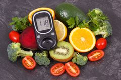Glucometer with result of sugar level and fruits with vegetables, diabetes and nutritious dessert containing minerals and vitamins royalty free stock photography