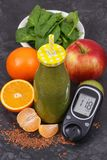 Glucometer with result sugar level and healthy smoothie from fruits and vegetables as source vitamins and minerals stock photos