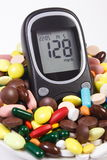 Glucometer with result sugar level and heap of medical pills and capsules, diabetes, health care concept Stock Photos