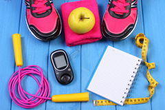 Glucometer, sport shoes, fresh apple and accessories for fitness on blue boards, copy space for text Royalty Free Stock Photos