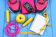 Glucometer, sport shoes, fresh apple and accessories for fitness on blue boards, copy space for text Stock Photos