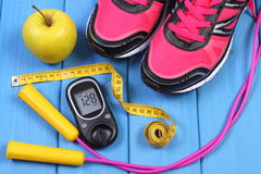 Glucometer, sport shoes, fresh apple and accessories for fitness on blue boards Royalty Free Stock Photos