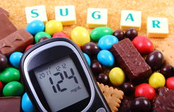 Glucometer, sweets and cane brown sugar with word sugar, unhealthy food Royalty Free Stock Photos