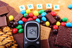 Glucometer, sweets and cane brown sugar with word sugar, unhealthy food Stock Image