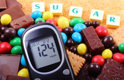 Glucometer, sweets and cane brown sugar with word sugar, unhealthy food Stock Photos