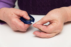 Glucometer und Blutung auf einem Finger lizenzfreie stockfotos
