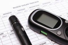 Glucometer und Lanzettengerät auf leeren medizinischen Formen für Diabetes Lizenzfreies Stockfoto