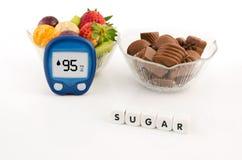 Glucometer und Schüssel mit Schokoladen und Früchten. Lizenzfreies Stockfoto