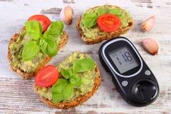 Glucometer y recientemente bocadillos con la goma del aguacate, de la diabetes, de la comida sana y de la nutrición imagen de archivo libre de regalías