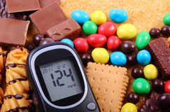 Glucometer z rozsypiskiem cukierki i trzcina brown cukier, niezdrowy jedzenie zdjęcie stock