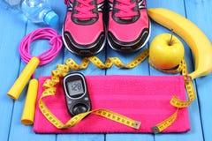 Glucometer, zapatos del deporte, frutas frescas y accesorios para la aptitud en tableros azules, espacio de la copia para el text Fotos de archivo