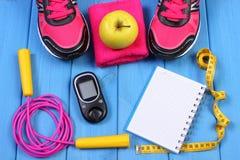 Glucometer, zapatos del deporte, manzana fresca y accesorios para la aptitud en tableros azules, espacio de la copia para el text Fotos de archivo libres de regalías