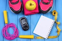 Glucometer, zapatos del deporte, manzana fresca y accesorios para la aptitud en tableros azules, espacio de la copia para el text Fotografía de archivo libre de regalías